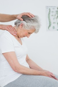 Side view of a senior woman getting the neck adjustment done in the medical office