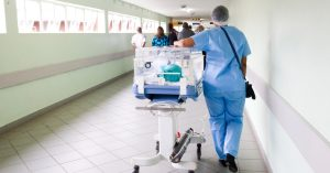 Person in scrubs in a medical setting walking down a corridor.