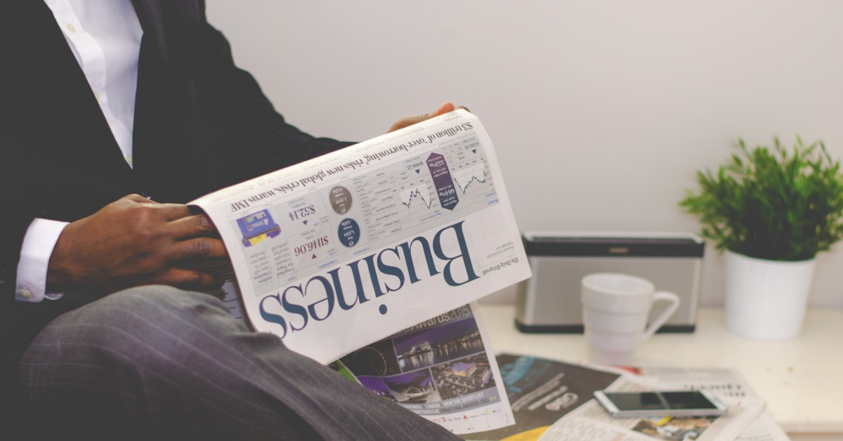 Close-up of a businessman in a crisp suit reading a business newspaper.