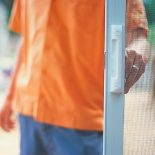 Image of a person opening a screen door