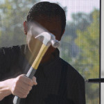 Image of a man hammering a screen