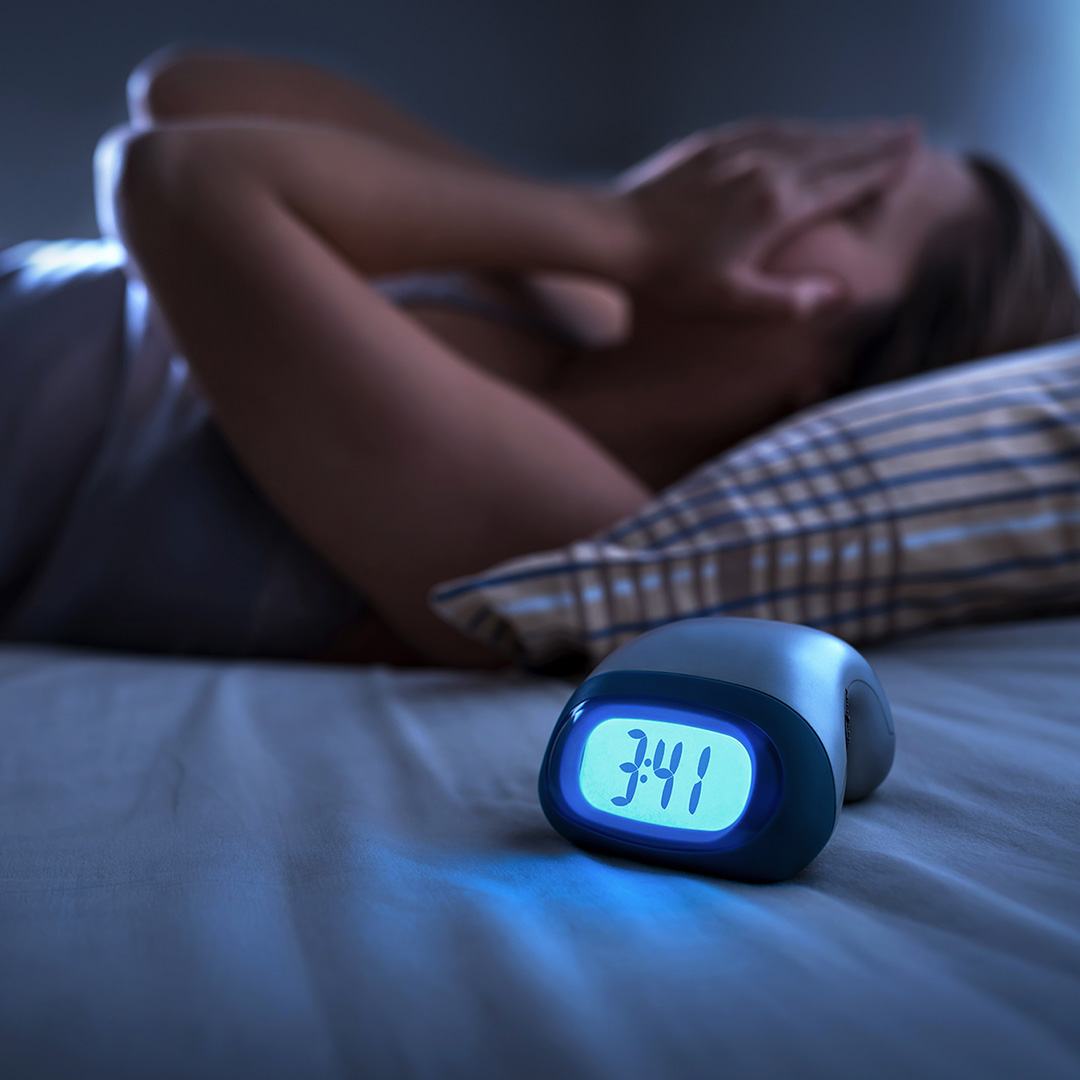 A woman lays on her back in bed with her hands over her eyes with a clock that says the time 3:41 am.