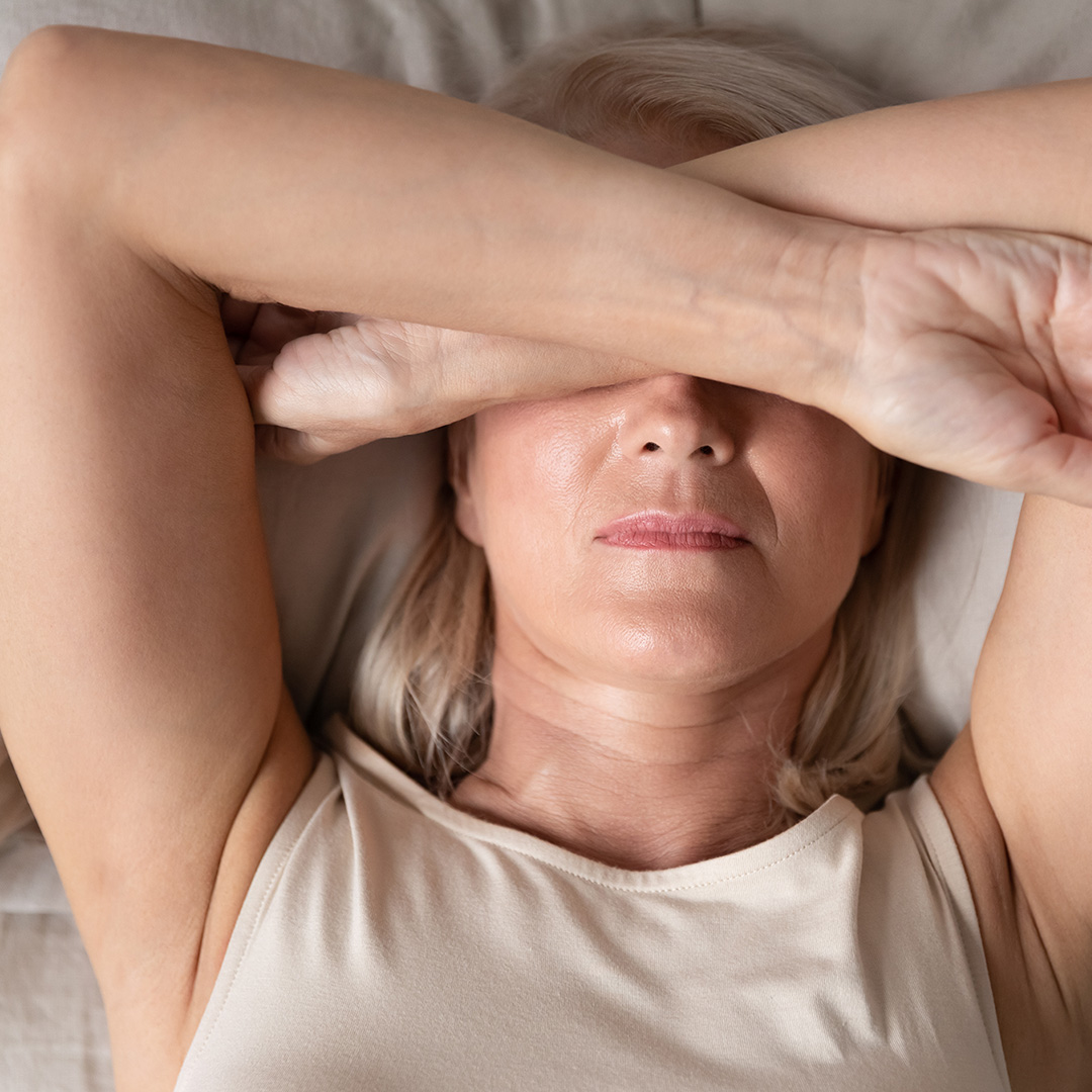 A woman laying on her back in bed with her arms covering her eyes.