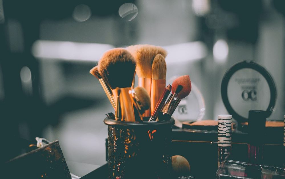 Assorted makeup brushes stand upright in a dark brass container. Photo by Raphael Lovaski on Unsplash.
