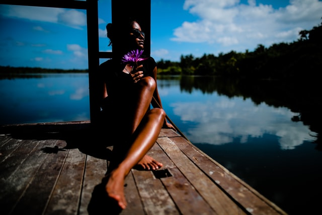 A woman sunbathes on the dock of a lake. Photo by Shifaaz shamoon on Unsplash.
