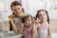 mom and daughters brushing their teeth and wearing pajamas