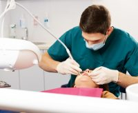 male dentist performing oral surgery on young female patient