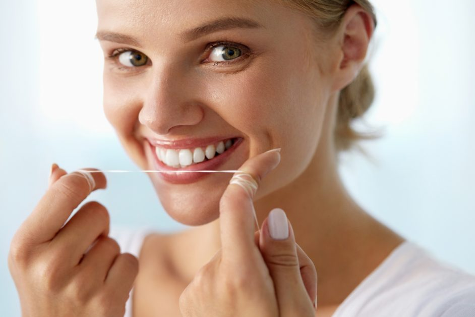 smiling woman holding length of dental floss