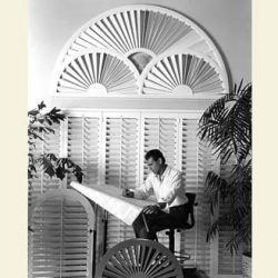 An image of a man looking at some design plans in front of some ornate window shutters.