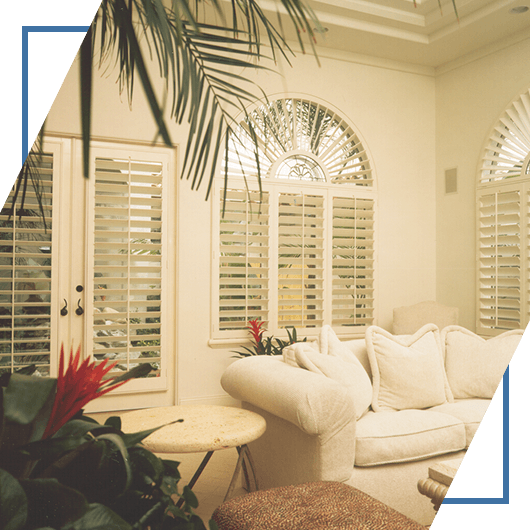 An image of a living room with plantation-style shutters designed by Shutters And More.