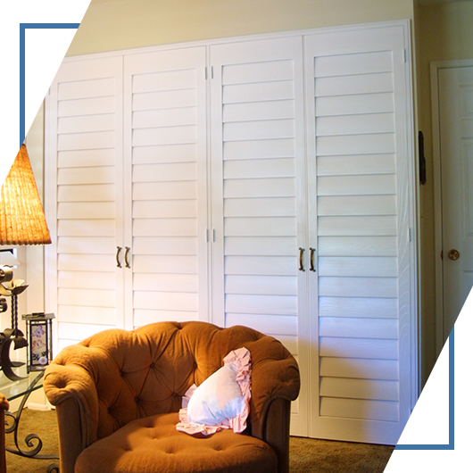 An image of a bedroom with eye-catching wooden closet doors, designed by Shutters And More.