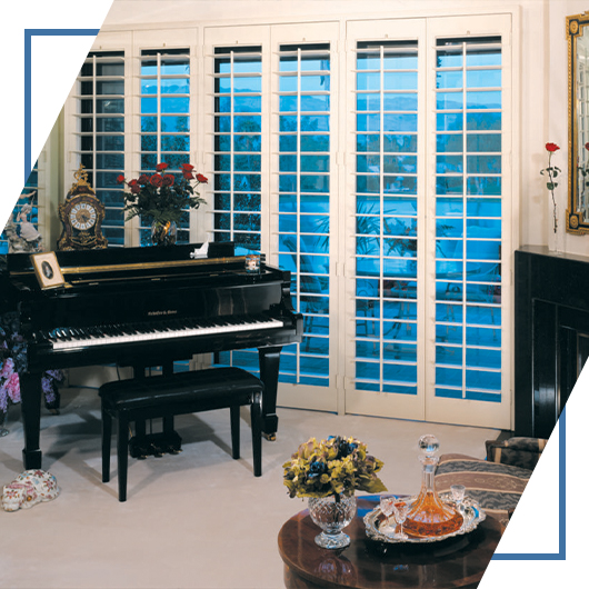 An image of a charming living room, the rear windows of which are beautified by sliding door shutters from Shutters And More.