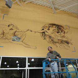 Our artist getting started on a custom wall mural
