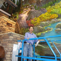 Our artist working on a custom wall mural of a mountain landscape