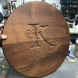 Sign maker completing custom wooden sign