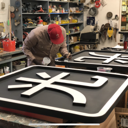 Painting custom business signage for an apartment complex
