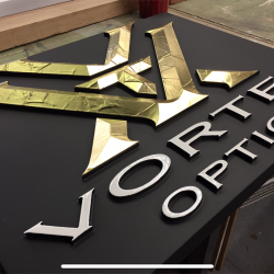Custom business signage for Vortex Optics in gold, black, and white