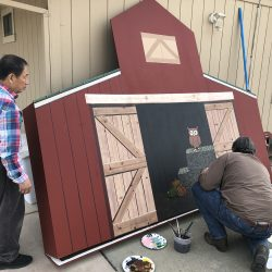 Painting a custom agriculture field sign of a barn for one of our clients