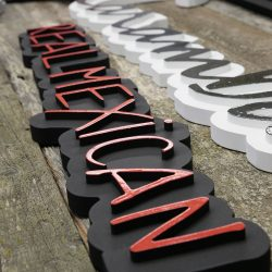Placing letters on custom wood signage for a Mexican restaurant