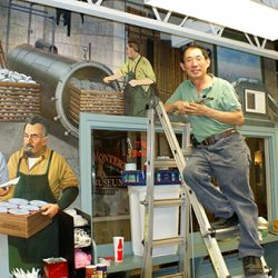Our artist posing next to the finished Monterey Canning Co. custom wall mural