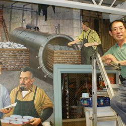 Our master artist posing next to the finished custom wall mural