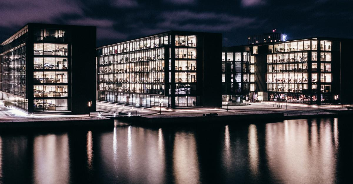 Business buildings at night with lights reflecting off water.