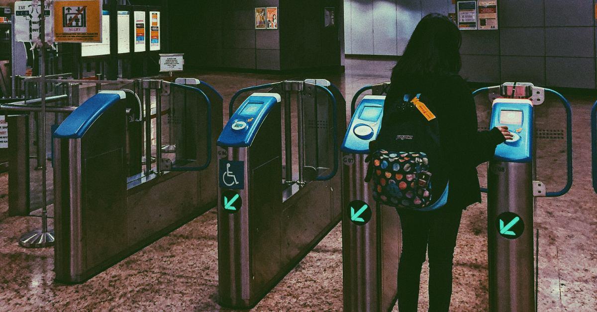 Woman going through self-service kiosks at a transportation center.