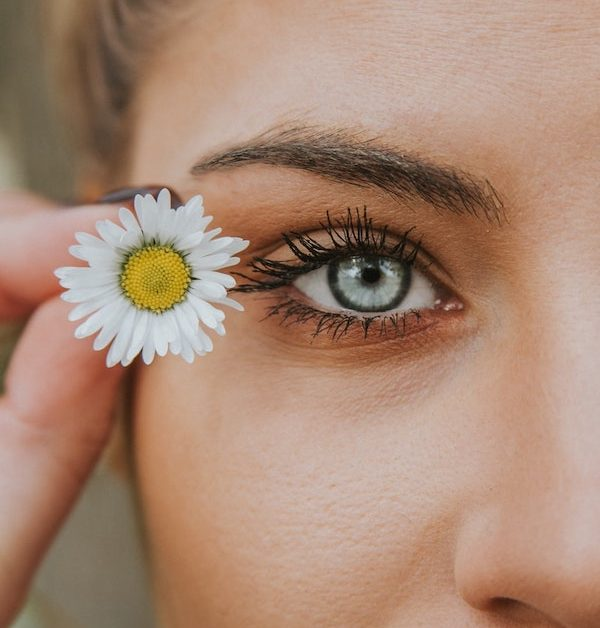 A woman holds a small white flower next to her clear blue eye. Photo by Angelos Michalopoulos on Unsplash.