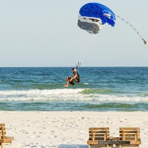 A skydiver landing on the beach.