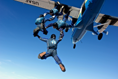 A group of skydivers jump out of the plane.
