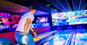 Man bowling down a neon-lit lane