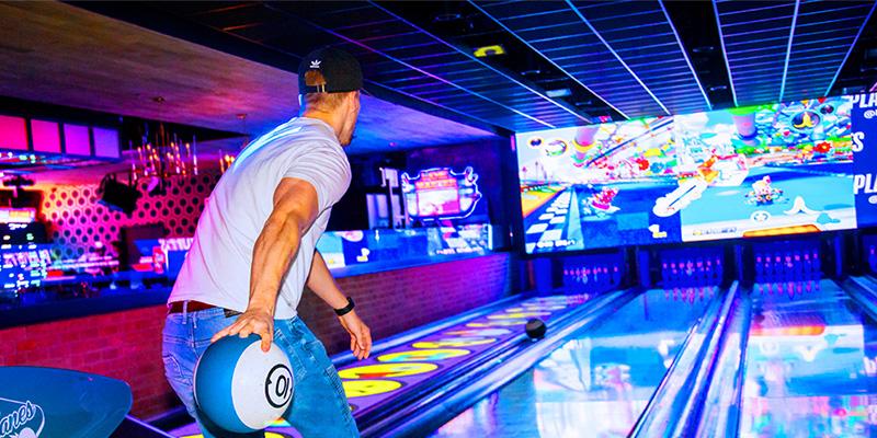 Man bowling down a neon-lit lane