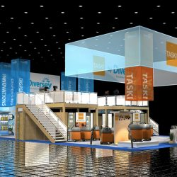 Huge island-style trade show display with hanging banners and two levels