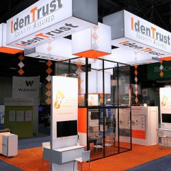 Orange and white trade show booth with glass booth