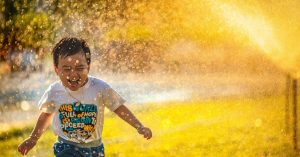 Smiling child running through sprinklers.