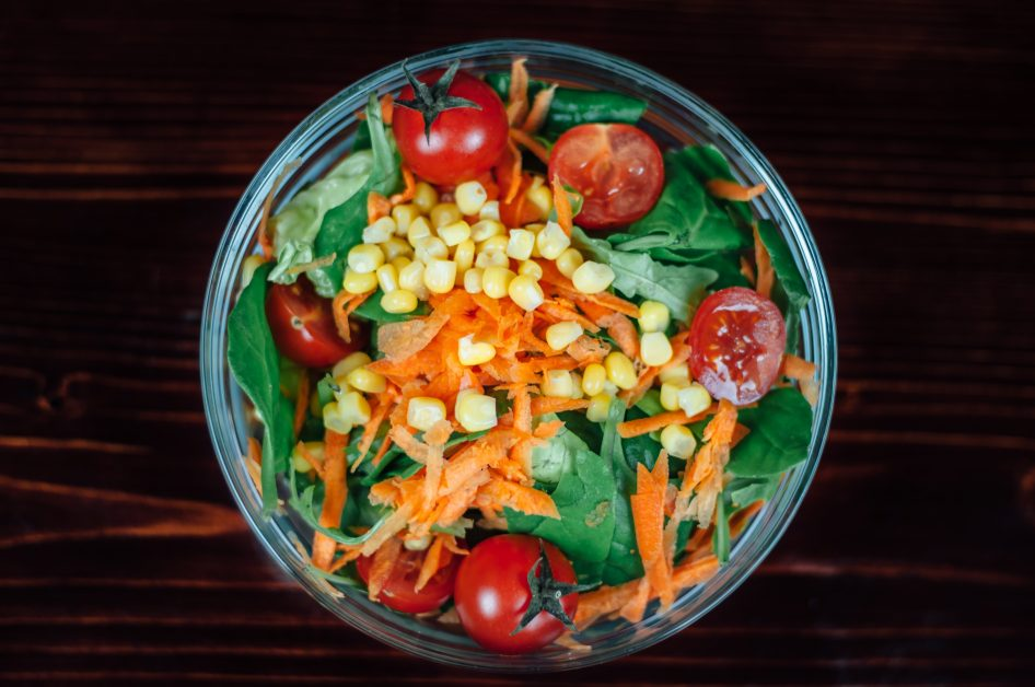 An image of a salad with carrots, tomatoes, and corn.