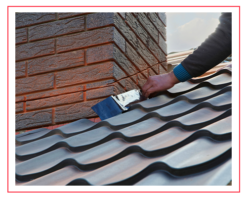 Image of a metal roofing contractor attaching a metal sheet to a chimney.