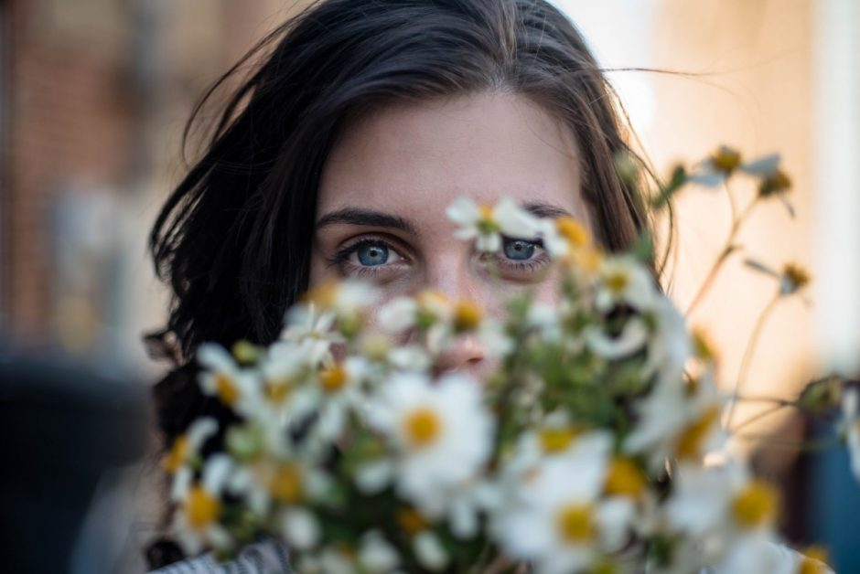 Young woman looking over a bouquet of flowers.