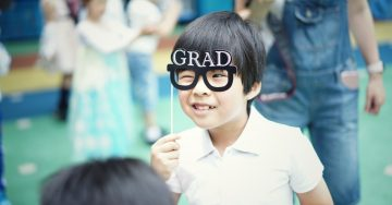 Smiling child holding paper glasses to his face.
