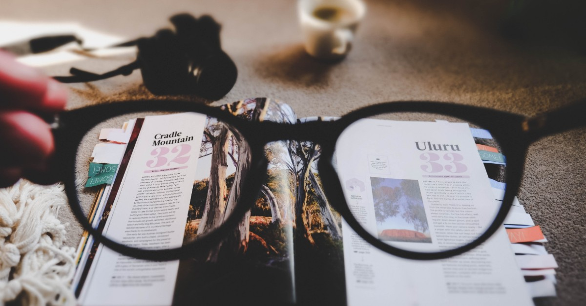 Looking through eyeglasses to see the print on a magazine page clearly.