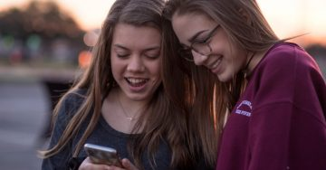 Teenagers looking at a phone screen.