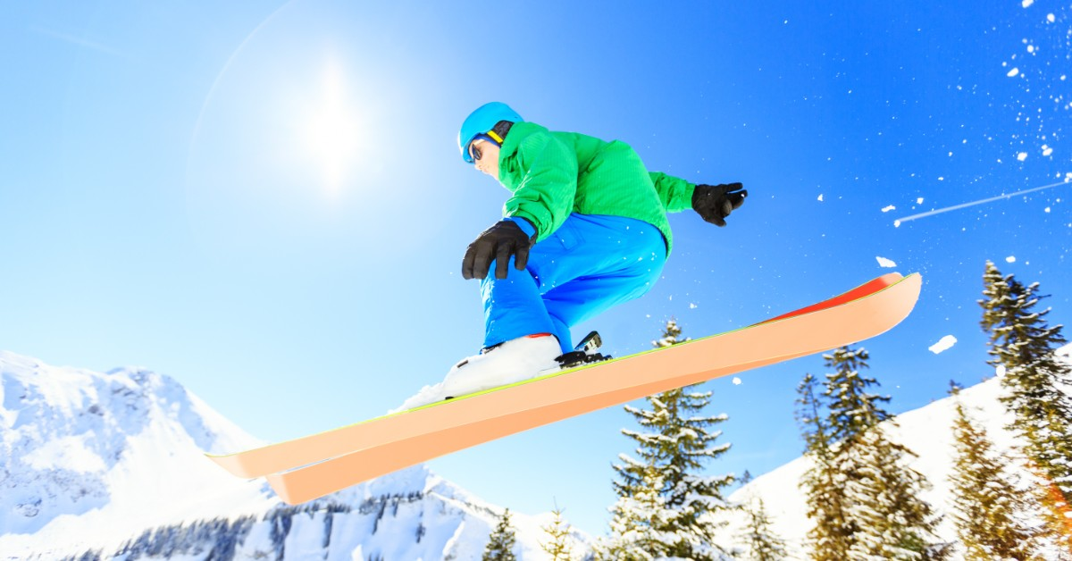 Person jump skiing against a blue sky and a snowy backdrop.