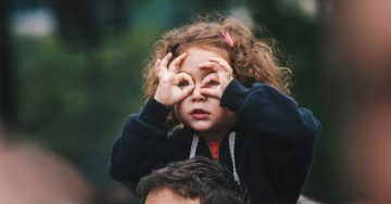 "A young girl sits on her father's shoulders and looks out into the distance, making ""binoculars"" with her fingers."