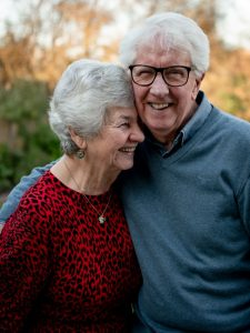 An elderly couple smiles during a warm embrace.