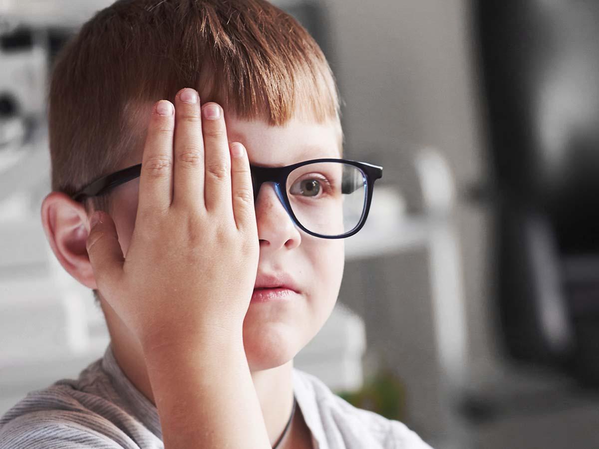 Young boy checking his vision at an eye exam.