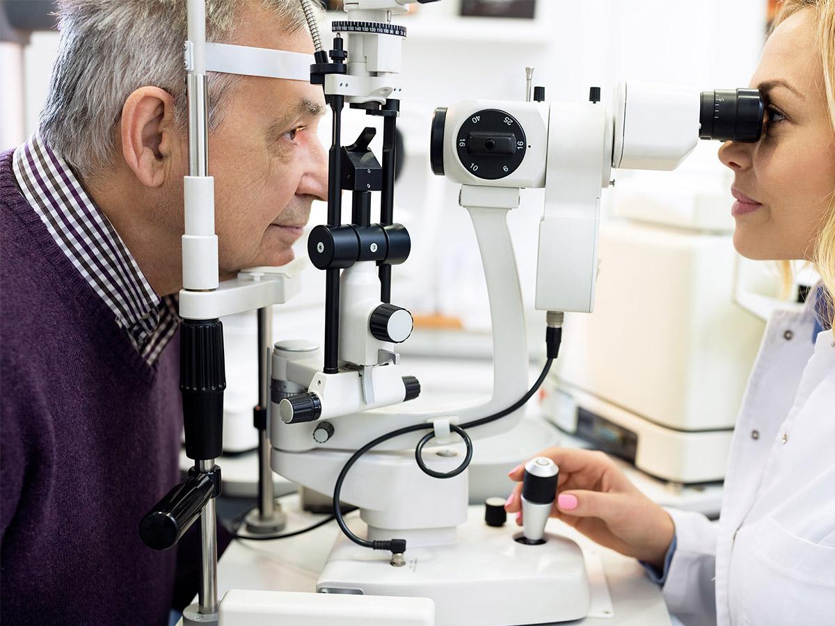 Elderly man getting an eye exam from an eye doctor.