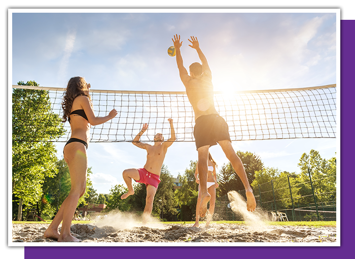 Playing beach volleyball while wearing prescription sports glasses.