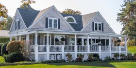 Gray wooden house with white balcony and grass yard