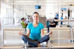 young woman doing yoga meditation at airport