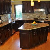 Kitchen with dark custom cabinets, gray/brown countertops, and stone backsplash - St Croix Cabinet Solutions